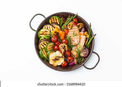 Seasonal, summer eating concept. Grilled vegetables and chicken breast in a pan on a white table, isolated. Top view flat lay background