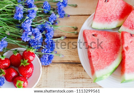 Seasonal summer flowers (blue cornflowers) and fruits (watermelon and strawberries) on rustic scorched wooden table