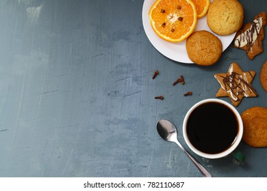 Seasonal table with orange, cookies and gingerbreads, coffee cup.