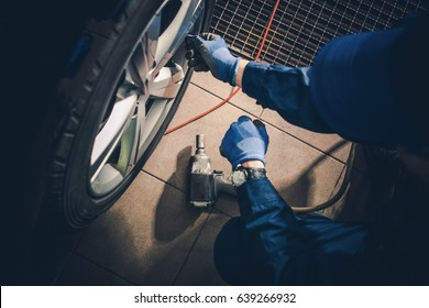Seasonal Tire Replacement. Car Service Worker Replacing Vehicle Tires and Rotate the Wheels.
