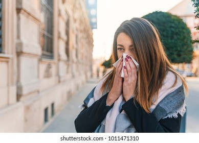 Seasonal virus infection. Sick young woman with seasonal influenza blowing her nose on a tissue. Woman has sneezing. This flu is getting to her. Young woman coughing covering her mouth with a tissue