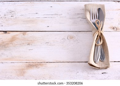 Seasonal white wooden plank table with silver cutlery.