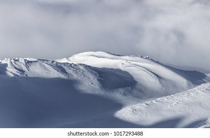 Seasonal winter landscape with snow capped mountain slopes. Altitude scenery. Background or wallpaper using landscape. Alpine mountains in Europe. Breathtaking untouched nature.