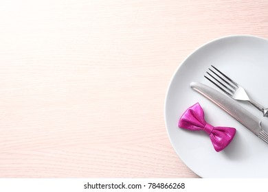 Seasonal wooden table with white dish, cutlery and pink bow.