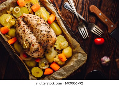 Seasoned chicken breast baked in oven with vegetables on baking sheet