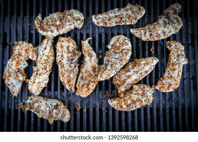 Seasoned chicken cooking on a grill.