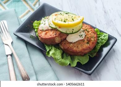 Seasoned crab cakes garnished with romaine lettuce sliced lemon and tartar sauce