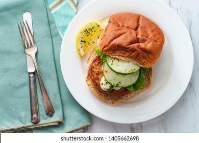 Seasoned fish cake sandwich on a whole wheat hamburger bun with creamy tartar sauce
