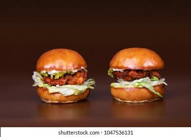 Seasoned grilled hamburger sliders on brown background
