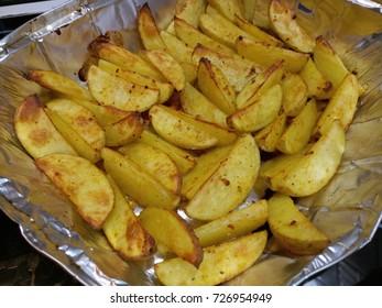 seasoned wedged potatoes baked in an aluminium tray