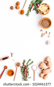 Seasoning background. Dry spices near ginger, garlic, rosemary on white background top view copy space