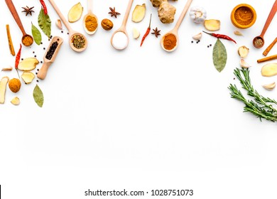 Seasoning background. Dry spices near ginger, garlic, rosemary, laurel leaf on white background top view copy space