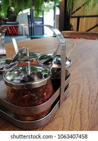 The seasoning set is on the brown table at the asia  noodle restaurant to prepare for customer to little cook the tasty of noodle. The seasoning set have a spicy, sugar, orange vinegar and fish sauce.