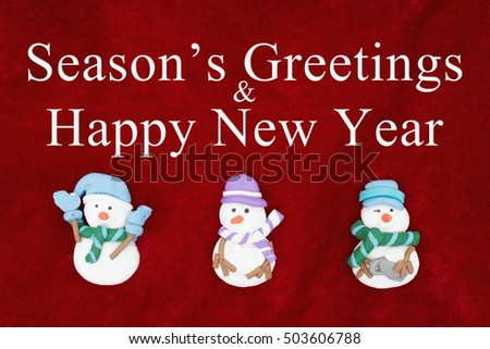 seasons greetings and happy new year greeting red plush fabric with three snowmen background with