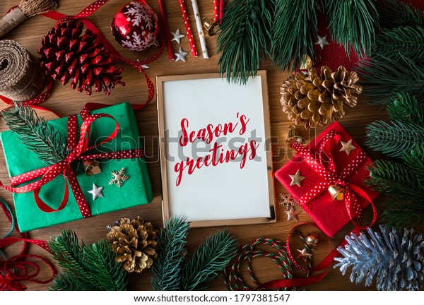 Season's greetings text on cards with gift box present and ornament element on wood table background.winter season activity ideas