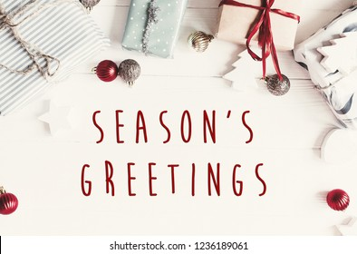 Season's greetings text on modern christmas flat lay with ornaments and gift boxes, top view with space for text. Holiday  greeting card. Merry Christmas and Happy new year