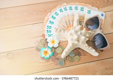 Seastar with sunglases on lot european money banknotes. Euro money and flowers on wooden backgrop as summer vacation and travel concept