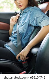 seat belt: woman hand fastening a seat belt in the car