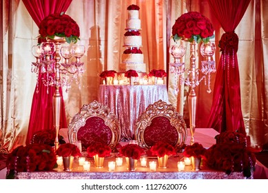 The seat for bride and groom of luxury indian wedding with wedding cake in background decoration with red roses theme and candle light in the sangeet night party