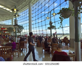 SEATAC, WA - APRIL 14, 2016: Travelers enjoy the relaxation, panoramic views, and architecture of the Central Terminal food and retail court at Seattle-Tacoma International Airport (Sea-Tac).