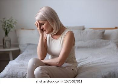 Sentada en la cama por la mañana, el tacto de mujer de mediana edad cara con los ojos cerrados de la mano sufre de presión barométrica dolor de cabeza migraña, la anciana se siente descontenta alterada la salud o el concepto de problemas personales