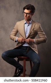 seated business man buttoning his suit and looks to side in studio