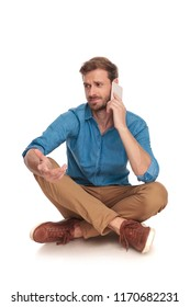 seated casual man is having a confusing discussion on the phone on white background