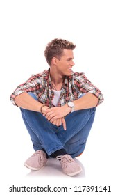seated casual young man looking to his side and smiling