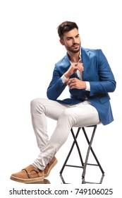 seated elegant man fixing his sleeve on white background