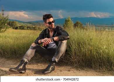 seated man wearing leather jacket looks away to side, he sits on the side of a country road