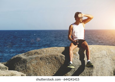 Seated on sea rock sports man resting after run while listening to music in headphones, male runner sitting on the background sky with copy space area for your text message or advertising content