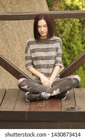 Seated sad young woman outdoor grunge style