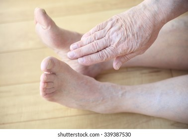 A seated senior man stretches a hand toward his toes.