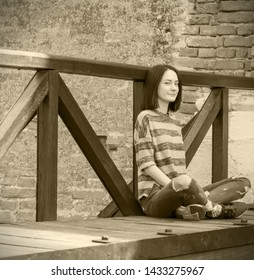 Seated smiled young woman outdoor grunge style