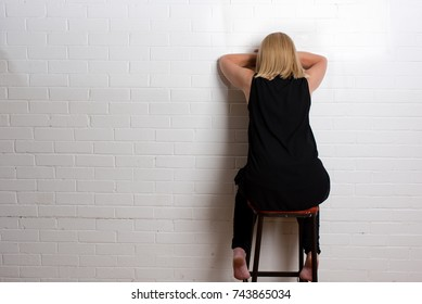 Seated white woman, back to camera with face hidden, leaning in to a brick wall with head on forearms  midlife crisis, feeling sad and lonely
