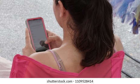 Seated woman using her cell phone