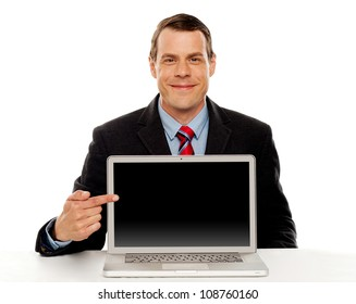 Seated young businessman pointing at blank laptop screen. Laptop facing camera