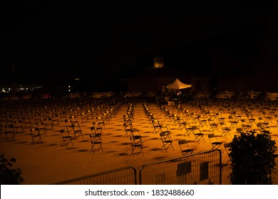 Seating arrangement for outdoors concert at night. spaced chairs separate for social distancing concept to avoid Coronavirus (COVID-19) pandemic contagion. preventive measure. - Shutterstock ID 1832488660