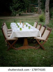 Seating for eight at a dinner table outdoors.