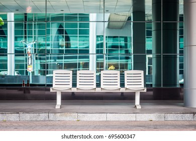 Seating at modern bus stop station. The white seats are made of metal.