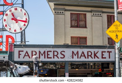 SEATLLE, WA - MAY 12: Unidentified worker paints entryway sign at Pike Place Market. May 12, 2016 in Phoenix, AZ.