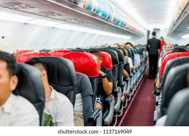 seats in the airplane and passenger sitting all area waiting for the plane taking off from runway.