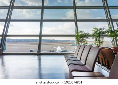 Seats in concourse area in airport. Near parking position of an airplane.