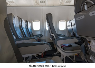 Seats, lunch trays with seat belts inside empty commercial airplane