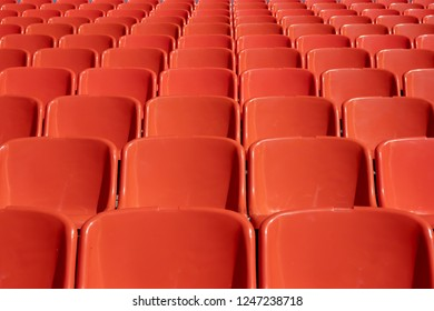 a lot of seats made of plastic orange for the audience, sitting under the sun on the backs of the glare from the sun