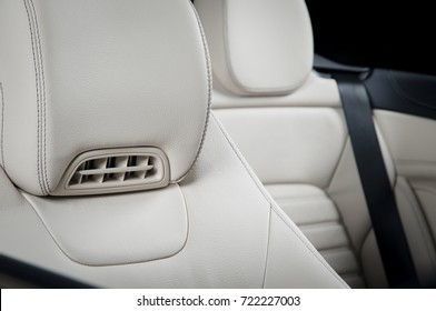 Seats in modern luxury car, white leather, car interior details with stitch