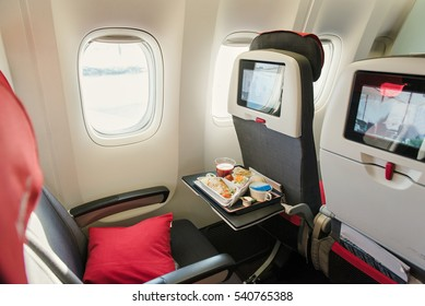 Seats on board of airplane. Cabin of economy class with information screens. Tasty meal served for the lunch on the table