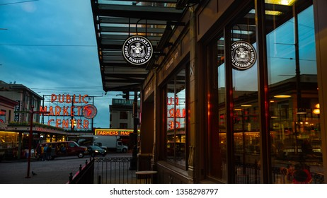 Seattle, WA—April 3, 2019; Reflection of Pike Place Market neon signs on the window of Starbucks Coffee during early morning blue light of cloudy day.