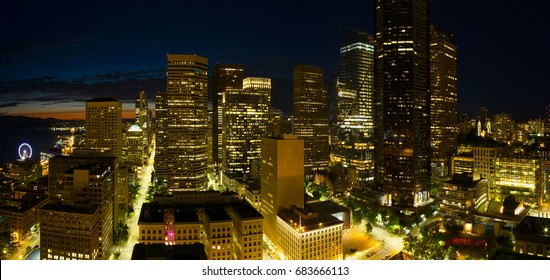 Seattle aerial night panorama of downtown and waterfront. Beautiful view of glittering city lights with some sunset color and deep blue night sky.