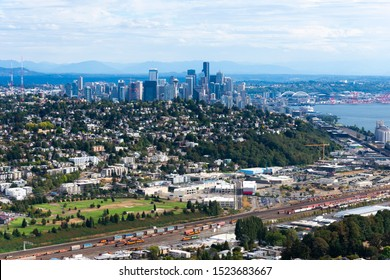 Seattle aerial overview from North showing a golf course, railway lines, residential houses, city center, water front and sports stadiums.